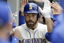 Seattle Mariners' Mac Williamson is congratulated in the dugout after hitting a two-run home run against the Baltimore Orioles during the fourth inning of a baseball game, Sunday, June 23, 2019, in Seattle. (AP Photo/John Froschauer)