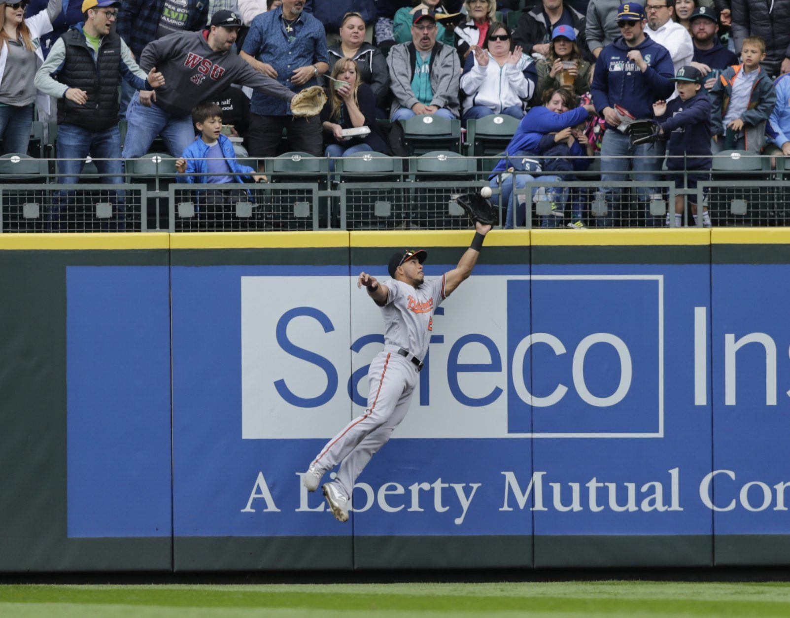 Baltimore Orioles right fielder Anthony Santander leaps to catch a fly ball hit by Seattle Mariners' Domingo Santana during the first inning of a baseball game, Sunday, June 23, 2019, in Seattle. (AP Photo/John Froschauer)