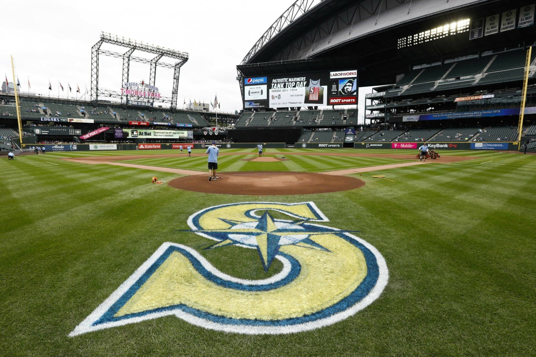 Groundskeepers prepare the infield before a baseball game between the Baltimore Orioles and the Seattle Mariners, Saturday, June 19, 2019, in Seattle. (AP Photo/Joe Nicholson)