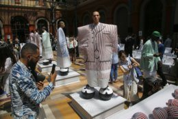 Guests take pictures of model at the Thom Browne mens Spring-Summer 2020 fashion collection presented in Paris, Saturday, June 22 2019. (AP Photo/Michel Euler)