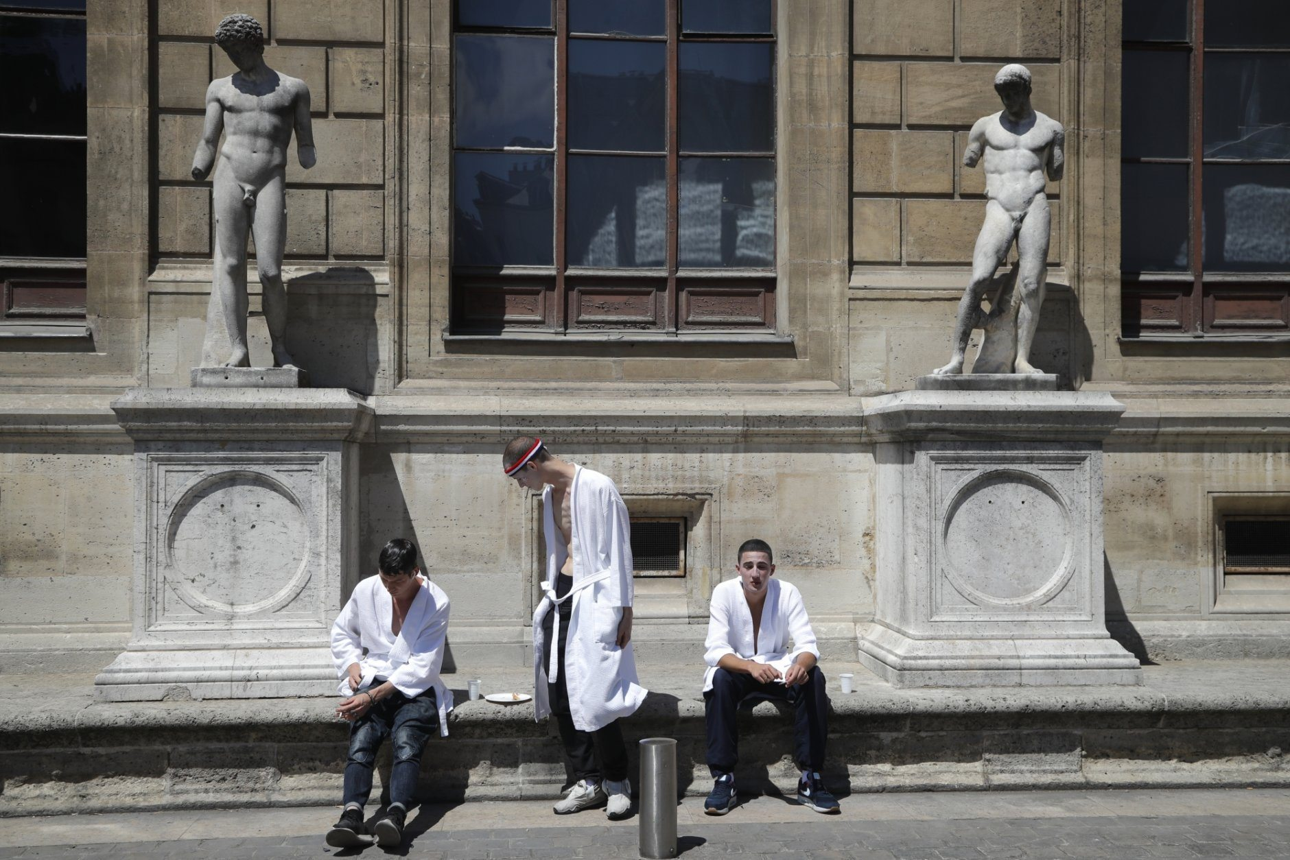 Models wait outside prior to the Thom Browne mens Spring-Summer 2020 fashion collection presented in Paris, Saturday, June 22 2019. (AP Photo/Michel Euler)