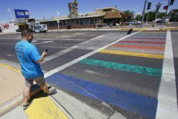 Craig LaBerge Esparza president of Albuquerque Pride surveys damage Thursday June 6, 2019, caused by motorcyclists to a Rainbow crosswalk on Central Ave., in Albuquerque, New Mexico in observance of Pride Week. (Adolphe Pierre-Louis/The Albuquerque Journal via AP)
