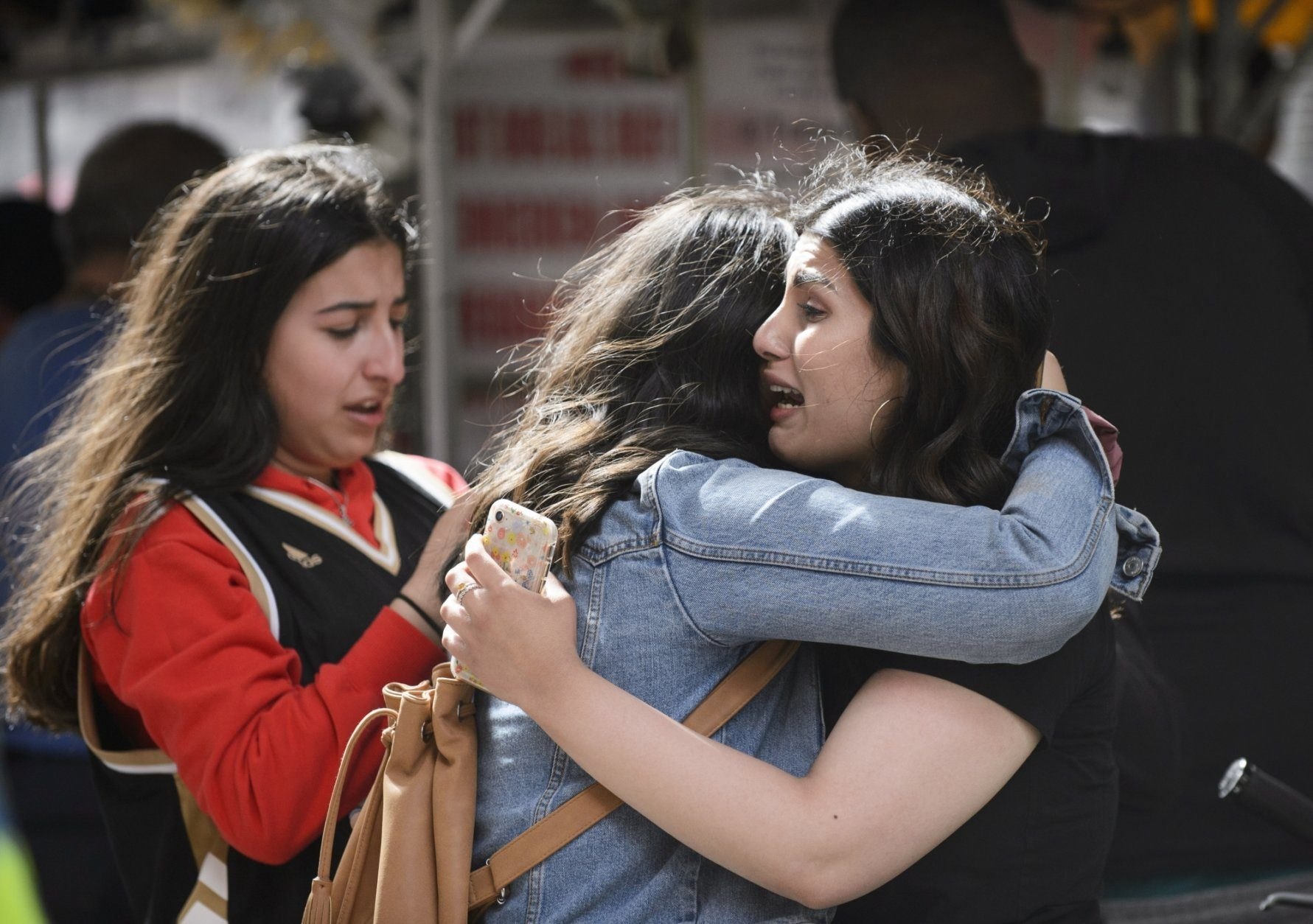 Friends embrace after shots were fired during the Toronto Raptors NBA basketball championship parade in Toronto, Monday, June 17, 2019. (Andrew Lahodynskyj/The Canadian Press via AP)
