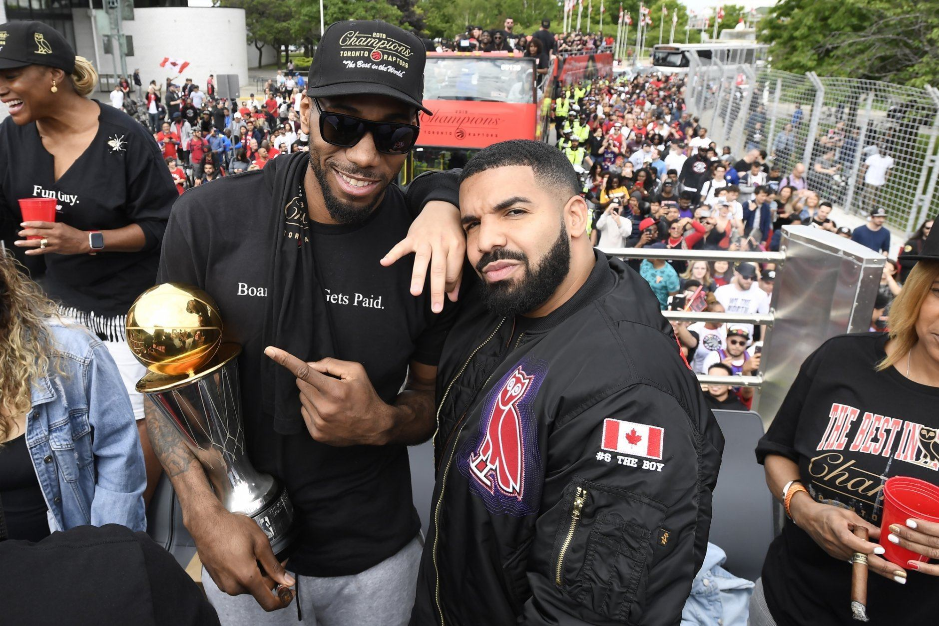 Toronto Raptors forward Kawhi Leonard points at his playoffs MVP trophy as he poses with performing artist Drake during the 2019 Toronto Raptors NBA basketball championship parade in Toronto, Monday, June 17, 2019. (Frank Gunn/The Canadian Press via AP)