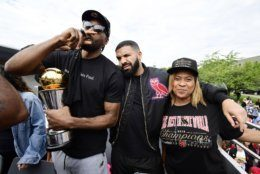 Toronto Raptors forward Kawhi Leonard, left to right, smokes a cigar holding his playoffs MVP trophy as he celebrates with performing artist Drake and his mother Kim Robertson during the 2019 Toronto Raptors NBA basketball championship parade in Toronto, Monday, June 17, 2019. (Frank Gunn/The Canadian Press via AP)