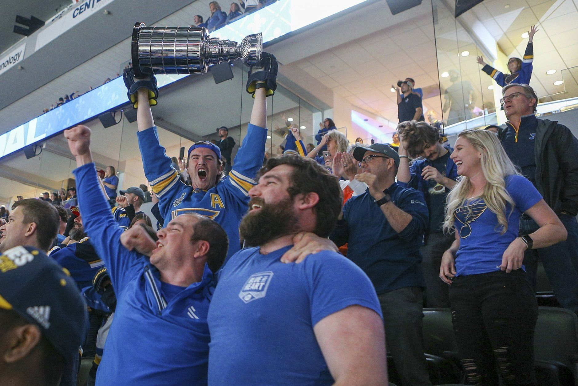 St. Louis Blues fans cheer as they watch television coverage of Game 7 of the team's NHL hockey Stanley Cup Final against the Boston Bruins, at the Enterprise Center on Wednesday, June 12, 2019, in St. Louis. (AP Photo/Scott Kane)