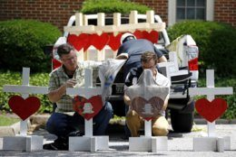 Volunteers prepare to place crosses for victims of a mass shooting at the municipal building in Virginia Beach, Va., at a nearby makeshift memorial, Sunday, June 2, 2019. (AP Photo/Patrick Semansky)