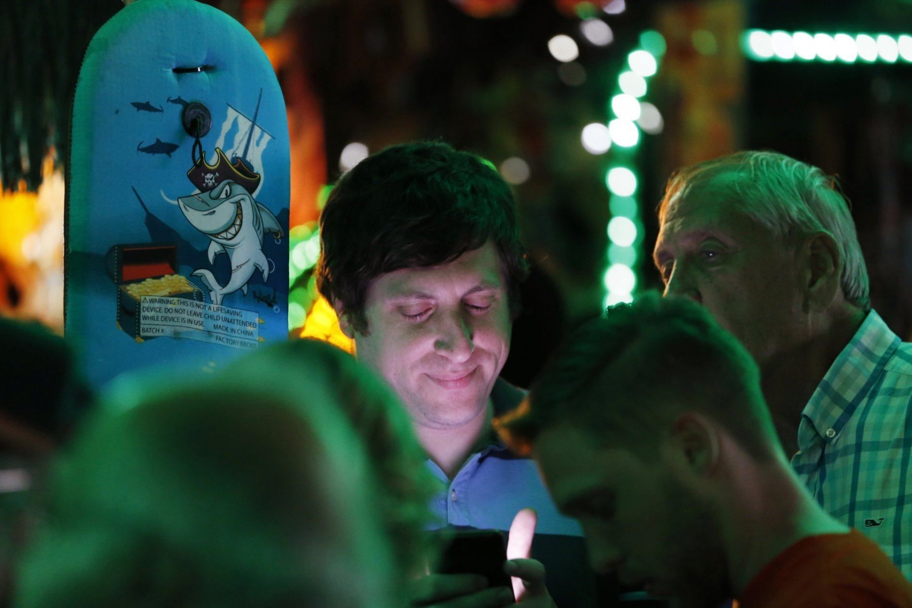 Supporters of state Sen. Richard Saslaw, D-Fairfax, are illuminated by cell phone screens as they check results at an election party in Springfield, Va., Tuesday, June 11, 2019. Saslaw is in a close race with his first primary opponent in 39 years. (AP Photo/Steve Helber)