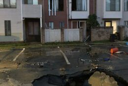 A water main break opens up a sinkhole in a town house complex in Montgomery County, Maryland, on Thursday, June 6, 2019.  (Courtesy Montgomery County Fire and Rescue Service)