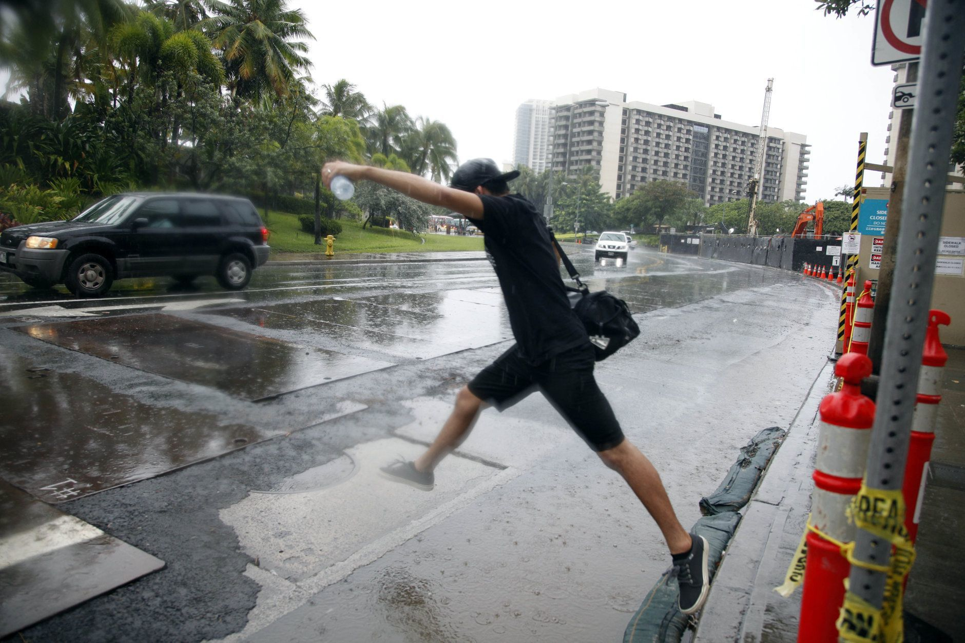 Ward Kea, of Honolulu, jumps over a puddle as he prepares to board a bus in Honolulu Sunday, Oct. 19, 2014. Hurricane Ana brought a steady rain to the Hawaiian Island of Oahu as it passed about 180 miles west. (AP Photo/P. Solomon Banda)