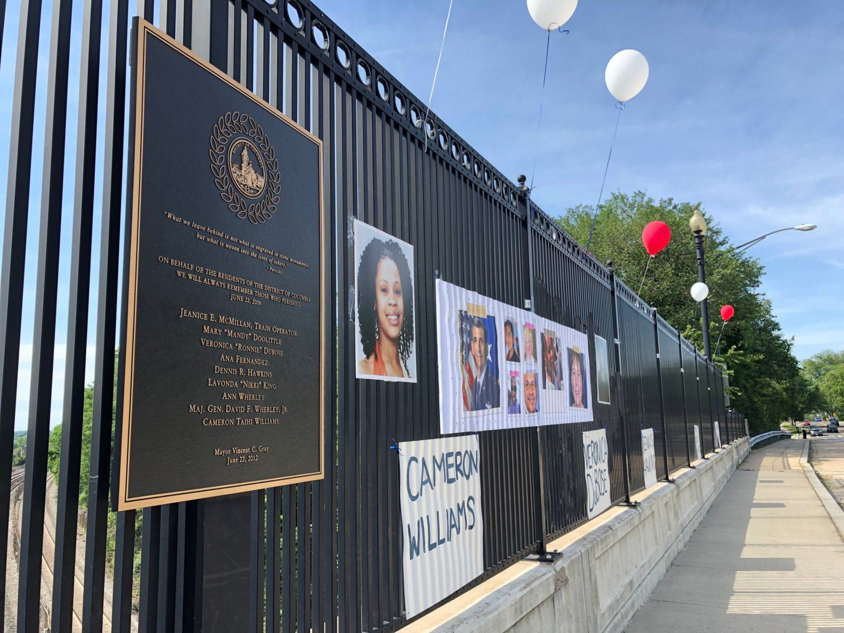 On the New Hampshire Avenue bridge over the tracks where the 2009 Metro crash happened, the names of those killed were posted along with photos. Red and white balloons were tied to the fence. (WTOP/Kate Ryan)