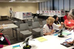 Volunteers were busy at the Reston precinct 223 even though turnout was low.  They had a lot of absentee ballots. (WTOP/Kristi King)