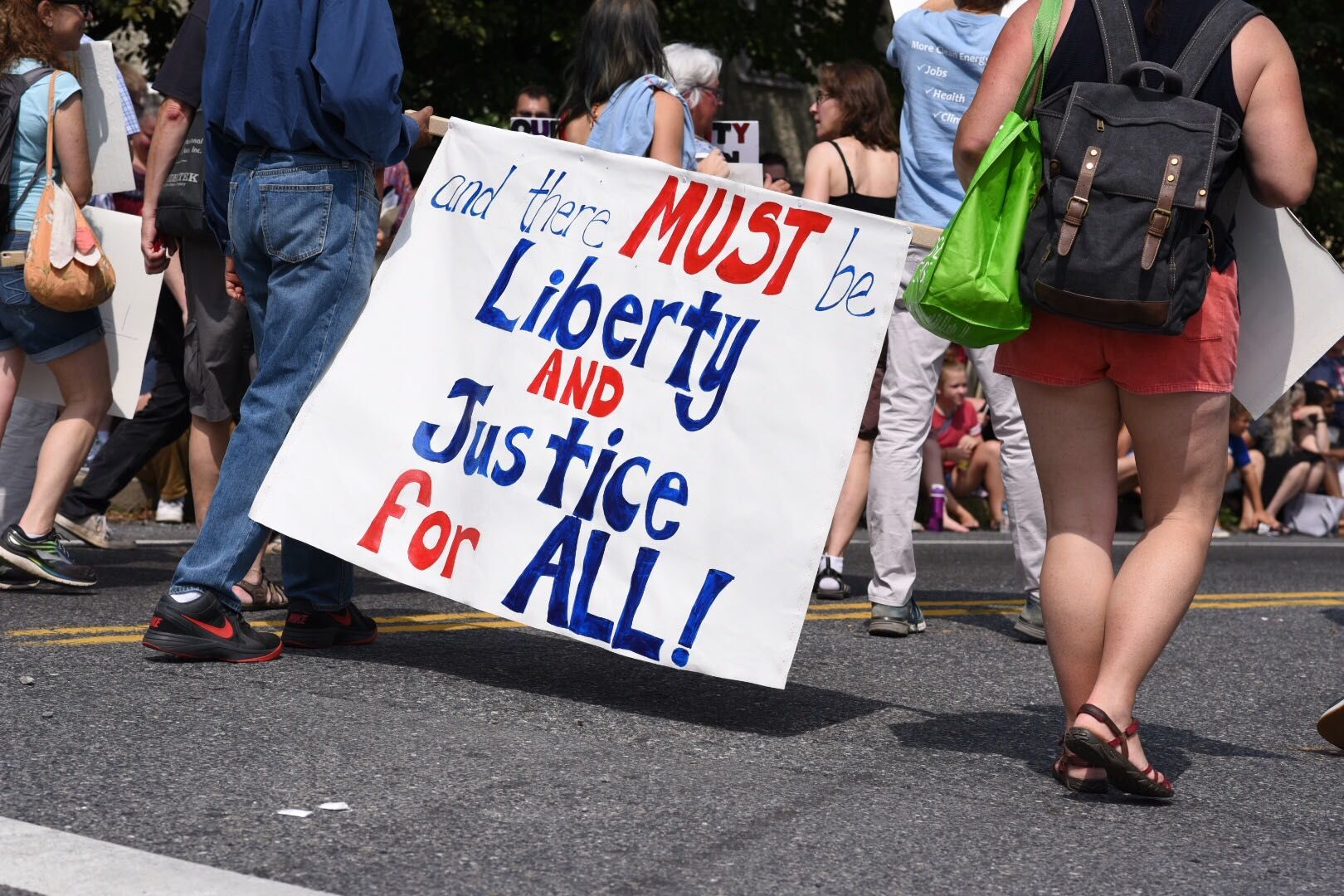 Signs with political messages dotted the Takoma Park Fourth of July Parade. (WTOP/Kate Ryan)