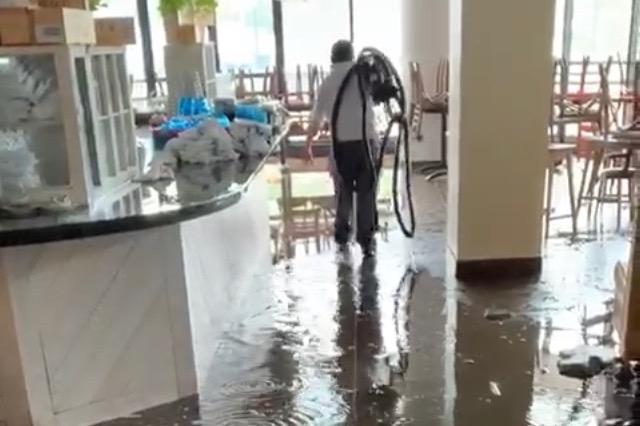 A worker walks through a flooded restaurant