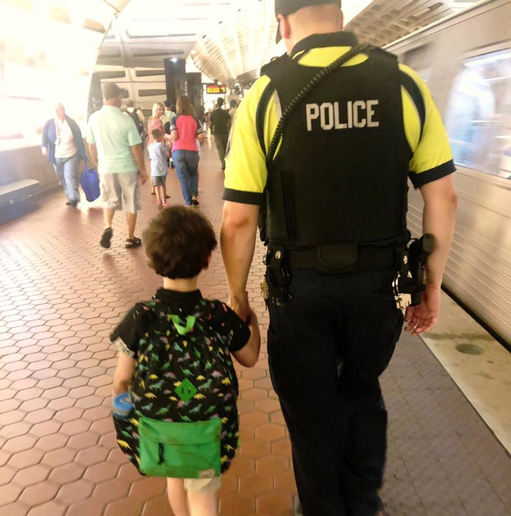 Transit officer walks with autistic boy