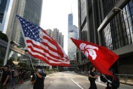 Protesters wave the Hong Kong and United States flag during a march in Hong Kong on Sunday, July 21, 2019. Tens of thousands of Hong Kong protesters marched from a public park to call for an independent investigation into police tactics. (AP Photo/Vincent Yu)