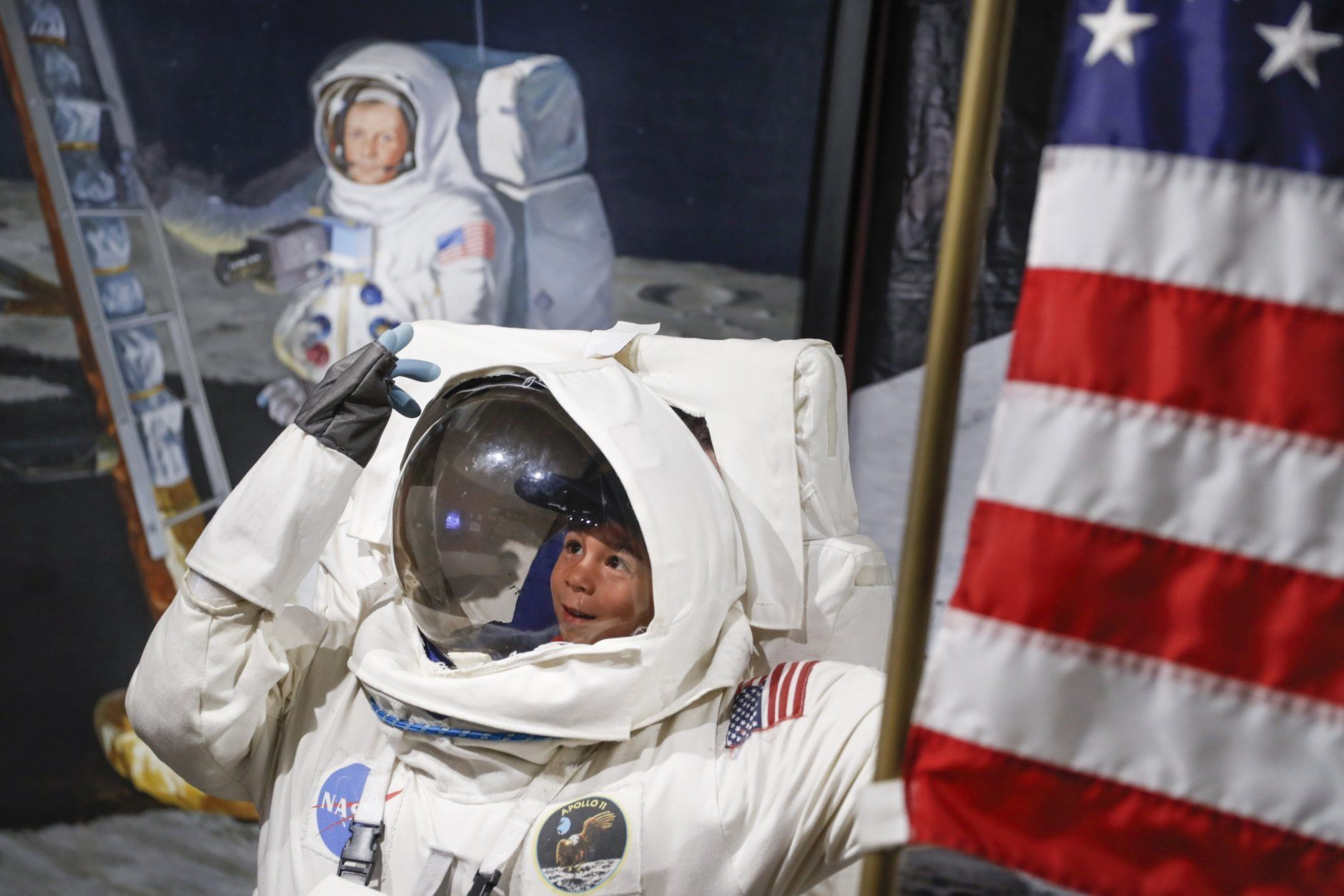 Visitors pose for photos beside a portrait of Neil Armstrong at the Armstrong Air & Space Museum as special events are underway for visitors commemorating the 50th anniversary of the first moon landing, Saturday, July 20, 2019, in Wapakoneta, Ohio. (AP Photo/John Minchillo)