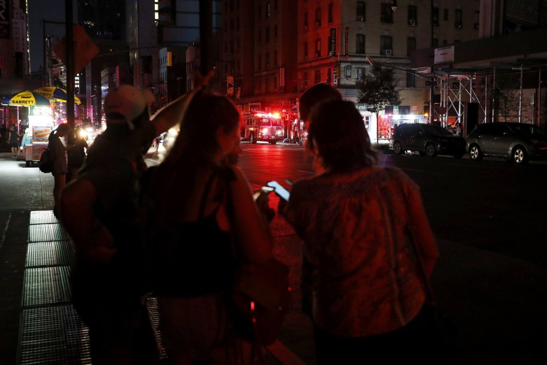Pedestrians looks at their cellphones during a power outage in midtown Manhattan, Saturday, July 13, 2019, in New York. Authorities were scrambling to restore electricity to Manhattan following a power outage that knocked out Times Square's towering electronic screens and darkened marquees in the theater district and left businesses without electricity, elevators stuck and subway cars stalled. (AP Photo/Michael Owens)