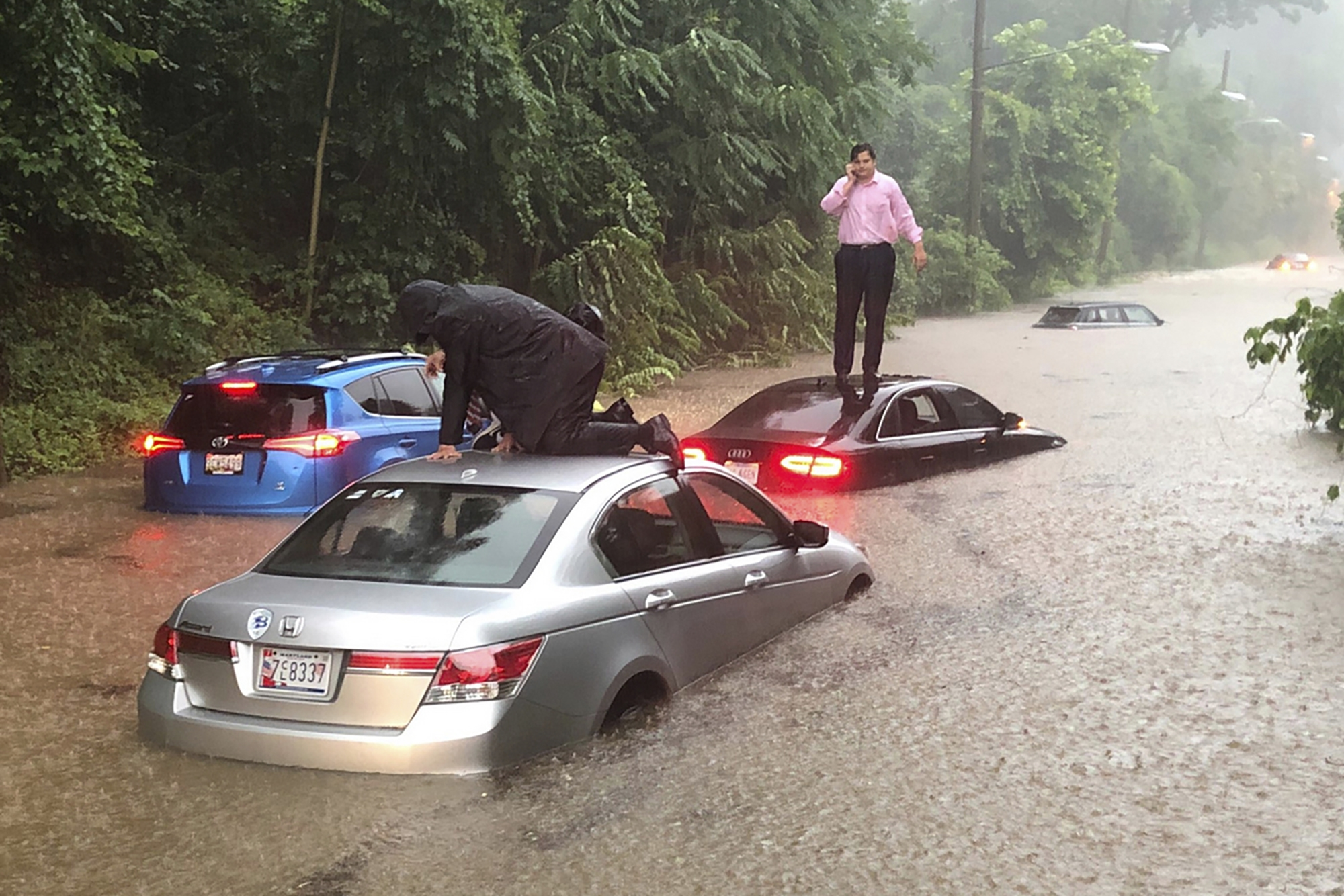 Man stranded by flood waters standing on roof of car