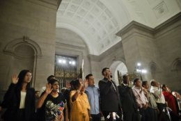 People raise their hands while taking the Oath of Allegiance during a naturalization ceremony in celebration of Independence Day at the National Archives in Washington, Thursday, July 4, 2019. (AP Photo/Pablo Martinez Monsivais)