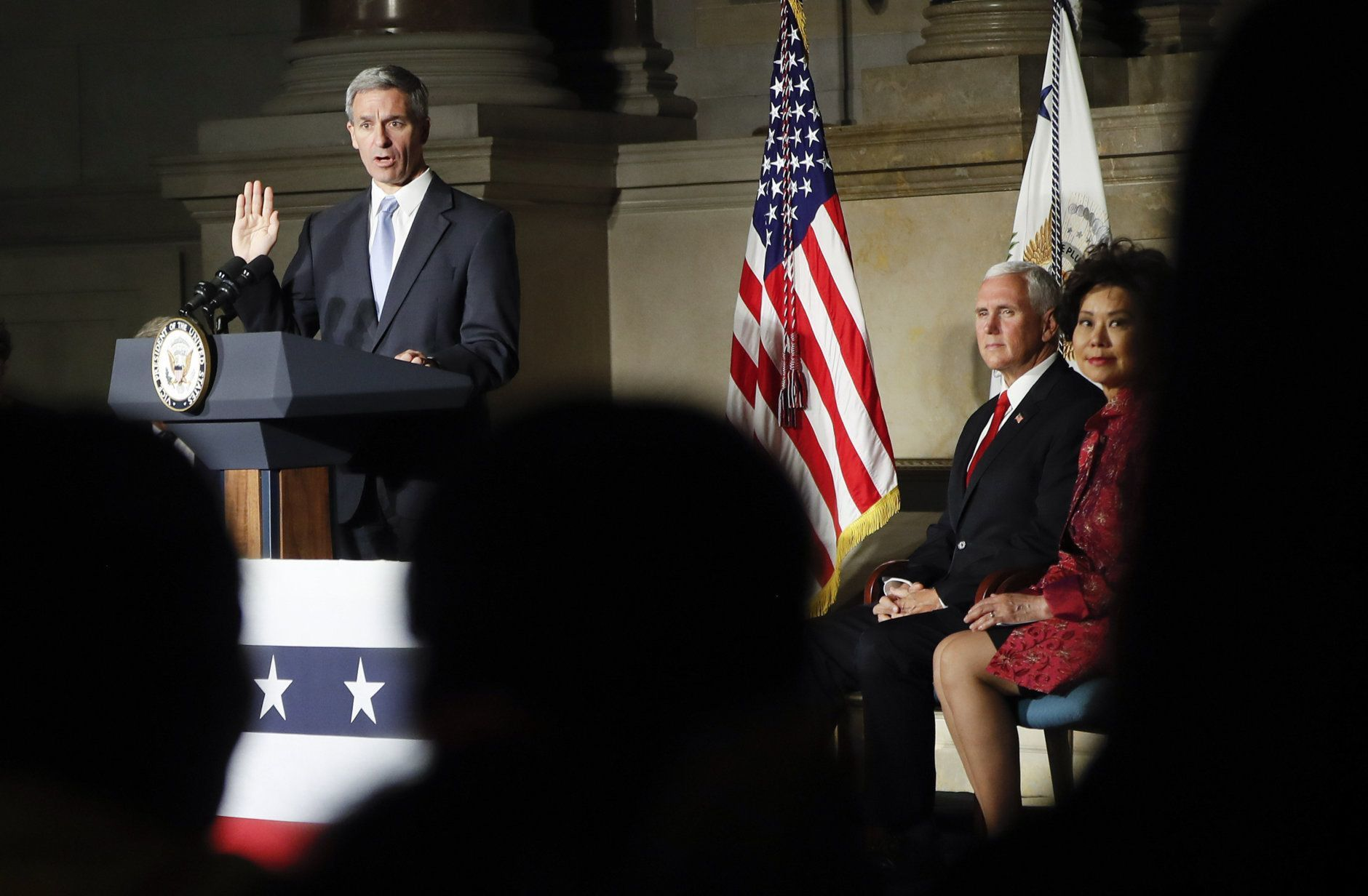 Acting Director, US Immigration and Immigration Services, Kenneth T. Cuccinelli, left, administers the Oath of Allegiance during a naturalization ceremony in celebration of Independence Day at the National Archives in Washington, Thursday, July 4, 2019. Also on stage are Vice President Mike Pence and Secretary of Transportation Elaine Chao, far right. (AP Photo/Pablo Martinez Monsivais)