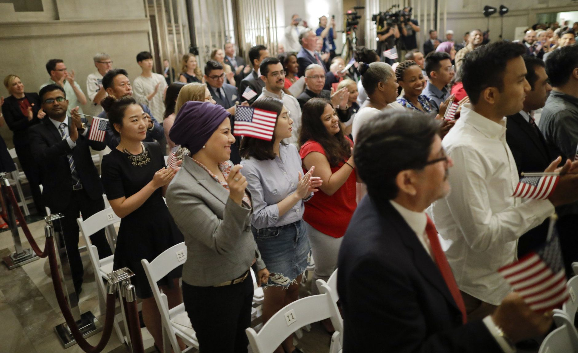 People begin celebrate after taking the Oath of Allegiance during a naturalization ceremony in celebration of Independence Day at the National Archives in Washington, Thursday, July 4, 2019. (AP Photo/Pablo Martinez Monsivais)