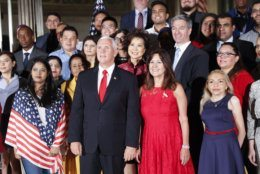 Vice President Mike Pence, center, his wife Karen Pence, to his right, pose for a group photo with new naturalized citizens following a naturalization ceremony in celebration of Independence Day at the National Archives in Washington, Thursday, July 4, 2019. Standing behind the Vice President are Secretary of Transportation Elaine Chao and Acting Director, US Immigration and Immigration Services, Kenneth T. Cuccinelli. (AP Photo/Pablo Martinez Monsivais)