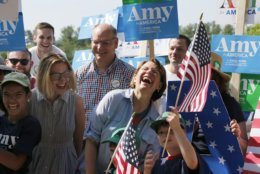 Democratic presidential candidate Sen. Amy Klobuchar, D-Minn., center, laughs with her husband John Bessler, and daughter Abigail Bessler, second from left, and as she greets her supporters during the Fourth of July Parade, Thursday, July 4, 2019, in Amherst. (AP Photo/Mary Schwalm)