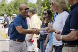 Democratic presidential candidate former U.S. Rep. John Delaney, D-Md., shakes hands with potential supporters along the route during the Fourth of July Parade, Thursday, July 4, 2019, in Amherst. (AP Photo/Mary Schwalm)