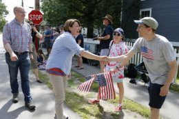 Democratic presidential candidate Sen. Amy Klobuchar, D-Minn., shakes hands with potential supporters along the route as her husband John Bessler looks on during the Fourth of July Parade, Thursday, July 4, 2019, in Amherst. (AP Photo/Mary Schwalm)