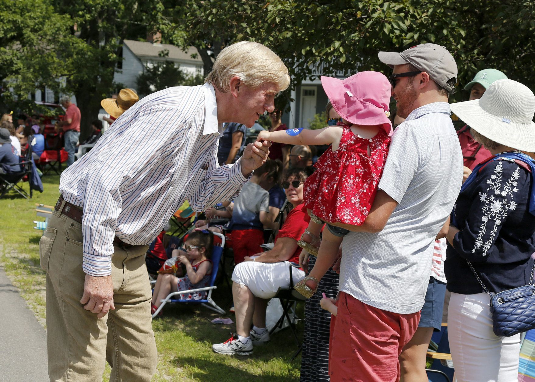Republican presidential candidate former Massachusetts Gov. William Weld leans in to kiss the hand of Abigail Smith, 2, of Concord, Mass., along the route during the Fourth of July Parade, Thursday, July 4, 2019, in Amherst. (AP Photo/Mary Schwalm)