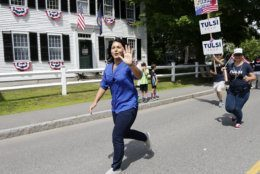 Democratic presidential candidate U.S. Rep. Tulsi Gabbard, D-Hawaii, waves along the parade route as she runs to catch up to her supporters during the Fourth of July Parade, Thursday, July 4, 2019, in Amherst. (AP Photo/Mary Schwalm)