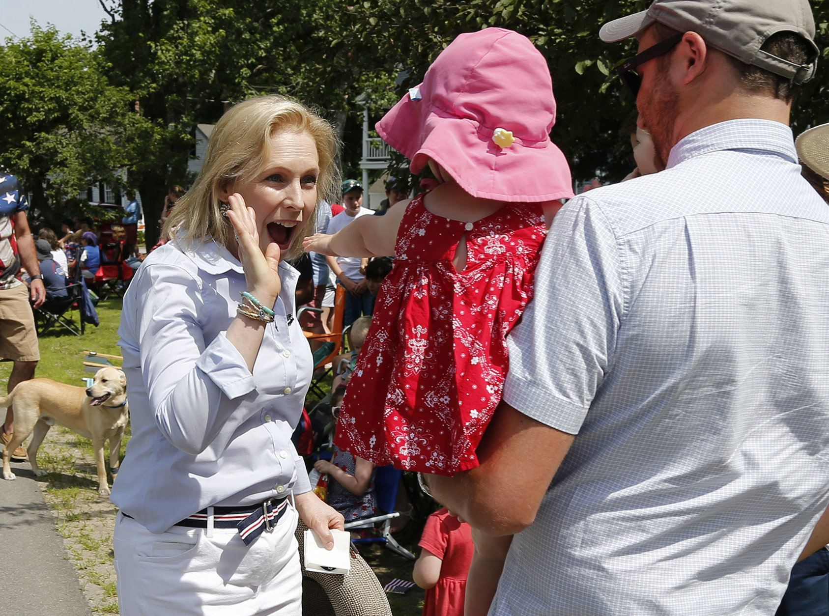 Democratic presidential candidate Sen. Kirsten Gillibrand, D-N.Y., gives a high-five to a child along the route during the Fourth of July Parade, Thursday, July 4, 2019, in Amherst. (AP Photo/Mary Schwalm)