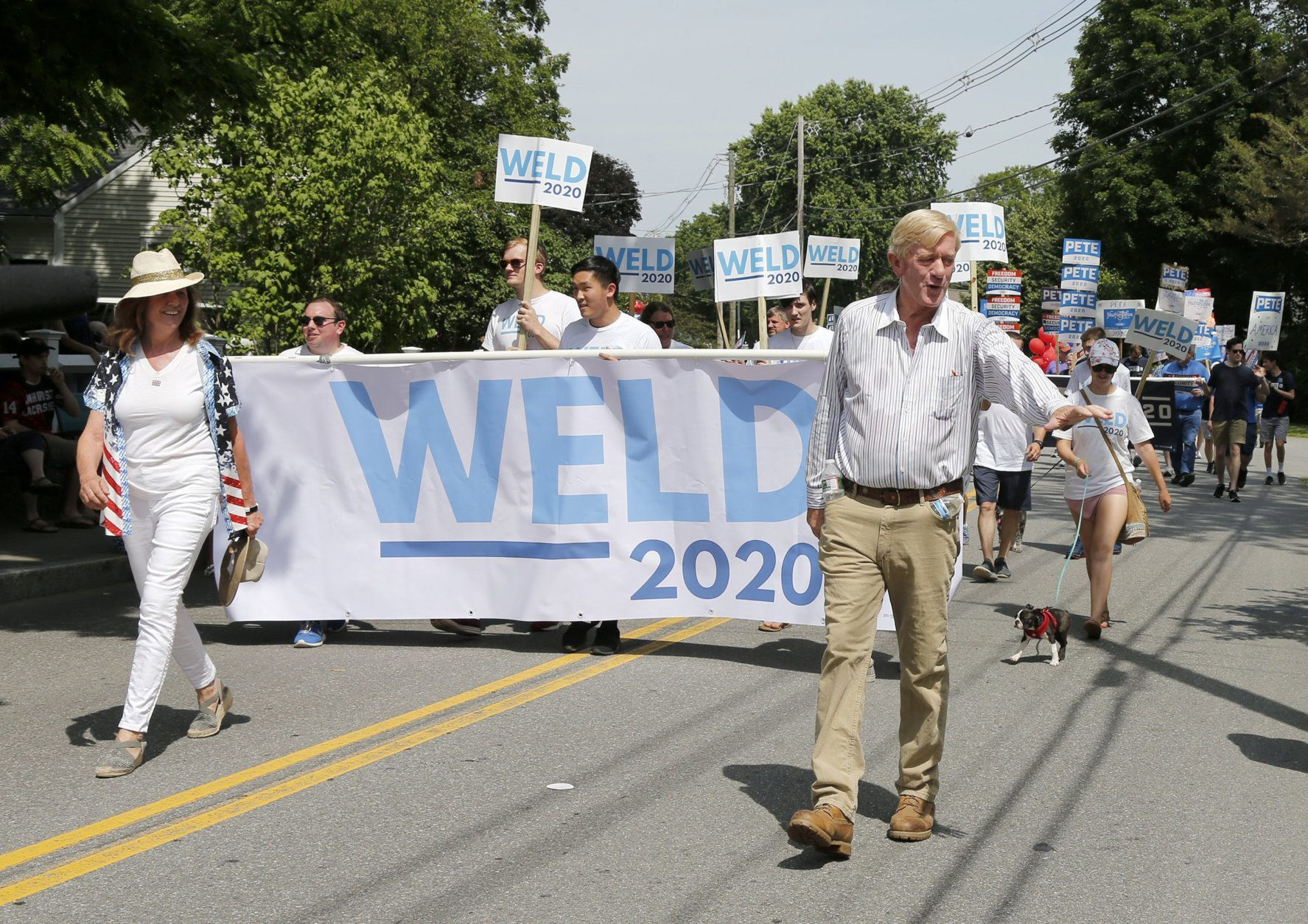 Republican presidential candidate former Massachusetts Gov. William Weld waves to potential supporters as he walks along the route with his wife Leslie Marshall during the Fourth of July Parade, Thursday, July 4, 2019, in Amherst. (AP Photo/Mary Schwalm)