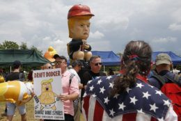 Protesters gather near a sculpture depicting President Donald Trump holding a cell phone on a toilet before Independence Day celebrations, Thursday, July 4, 2019, on the National Mall in Washington. (AP Photo/Patrick Semansky)
