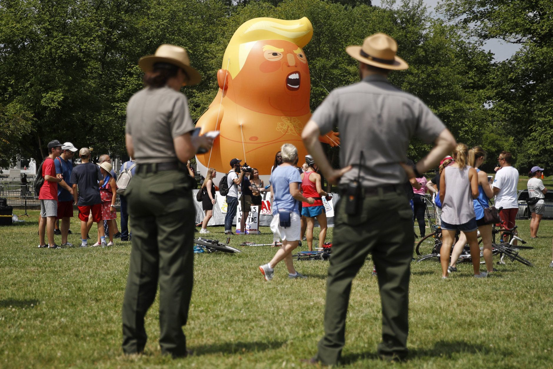 National Park Service rangers view a Baby Trump balloon before Independence Day celebrations, Thursday, July 4, 2019, on the National Mall in Washington. (AP Photo/Patrick Semansky)
