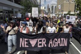 "Protestors assembled by a majority Jewish group called ""Never Again Is Now"" walk through traffic as they make their way to Independence Mall Thursday July 4, 2019, in Philadelphia. Hundreds gathered during the city's traditional Fourth of July parade to protest the treatment of immigrants and asylum seekers. (AP Photo/Jacqueline Larma)"