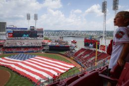 A giant United States flag is unfurled as the national anthem is played before a baseball game between the Cincinnati Reds and the Milwaukee Brewers, Thursday, July 4, 2019, in Cincinnati. (AP Photo/John Minchillo)
