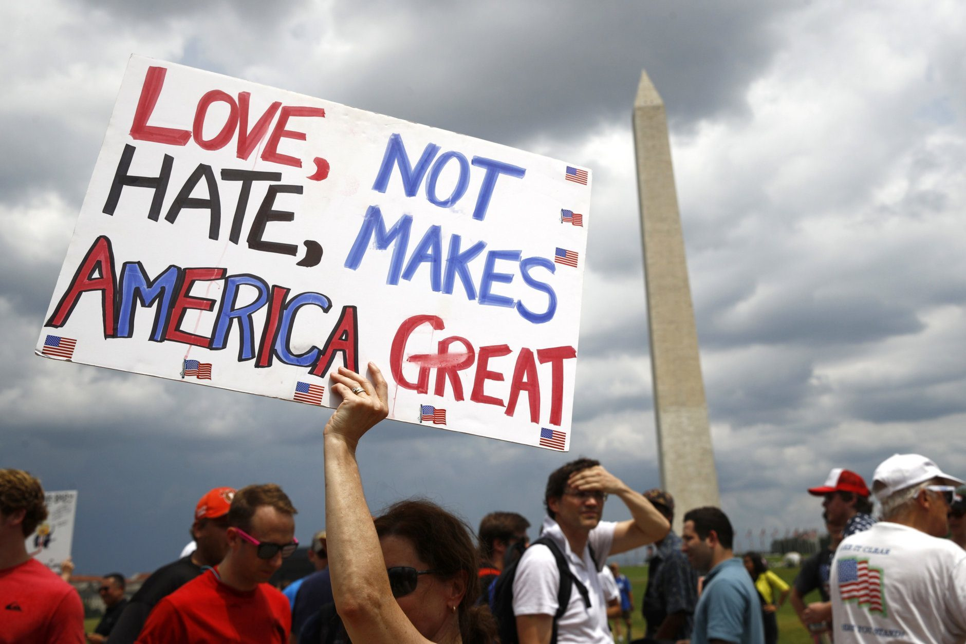 Kathleen Otal, of Arlington, Va., holds up a sign before Independence Day celebrations, Thursday, July 4, 2019, on the National Mall in Washington. (AP Photo/Patrick Semansky)