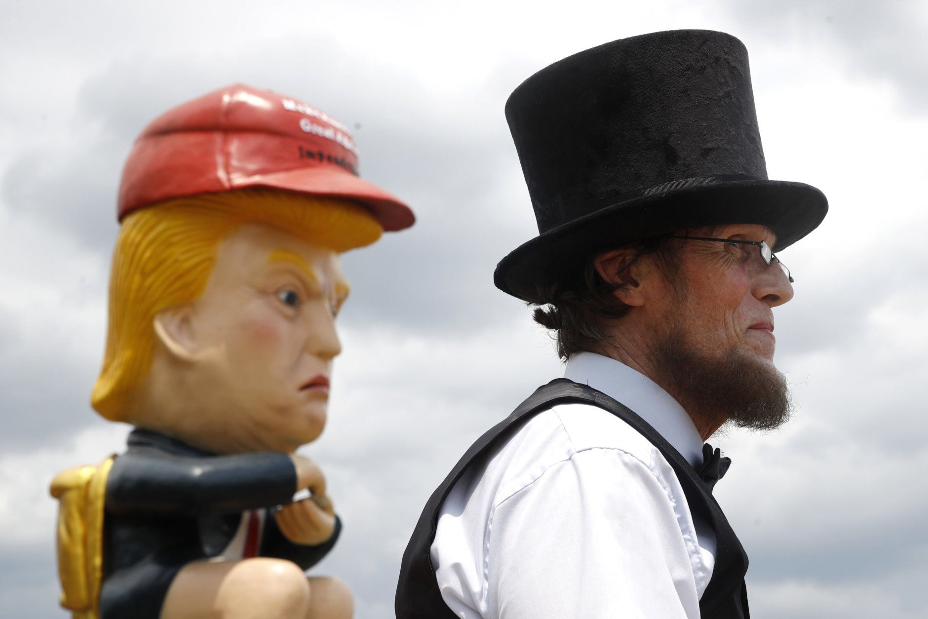 Everett Loud, of Corning, N.Y., and dressed as President Abraham Lincoln, stands near a sculpture of President Donald Trump holding a cell phone while sitting on a toilet before Independence Day celebrations, Thursday, July 4, 2019, on the National Mall in Washington. (AP Photo/Patrick Semansky)