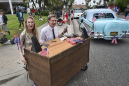 "Gray Bright, and Kyle McAuley arrive to participate in the Fourth of July parade with their motorized ""Late Nite"" desk to conduct interviews with scientists and tech people on Thursday, July 4, 2019 in Santa Monica, Calif. (AP Photo/Richard Vogel)"