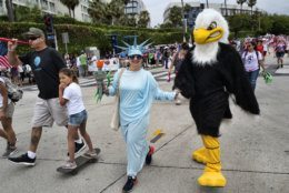 Dressed as Lady Liberty and the American Eagle participants parade down a street while joining in on the festivities at the Santa Monica Fourth of July parade, Thursday July 4, 2019 in Santa Monica, Calif. (AP Photo/Richard Vogel)