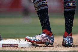 Washington Nationals' Victor Robles, right, stands on first wearing patriotic themed cleats during the sixth inning of a baseball game against the Miami Marlins, Thursday, July 4, 2019, in Washington. The Nationals won 5-2.(AP Photo/Nick Wass)