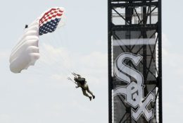 Frog-X parachute team member, retired U.S. Marine Marc Hogue glides toward the field before a baseball game between the Chicago White Sox and Detroit Tigers Thursday, July 4, 2019, in Chicago. (AP Photo/Mark Black)
