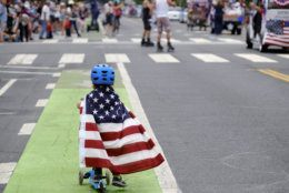 Two and a half year old Zacky Kaplan rides his scooter while draped in the American flag as he makes his way along the parade route during the Santa Monica Fourth of July Parade on Thursday, July 4, 2019 in Santa Monica, Calif. (AP Photo/Richard Vogel)