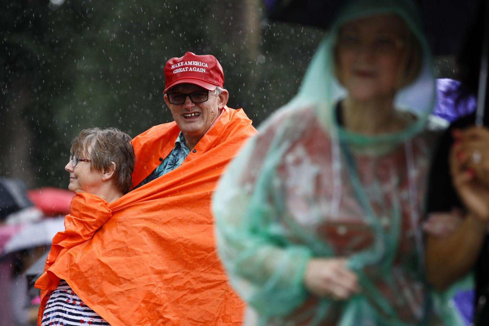 John Hood, back right, waits out rainfall alongside his wife, Kathy, before Independence Day celebrations, Thursday, July 4, 2019, on the National Mall in Washington. (AP Photo/Patrick Semansky)