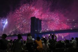 People on the east side of Manhattan watch a fireworks display, part of Independence Day festivities, Thursday, July 4, 2019, in New York. (AP Photo/Jeenah Moon)