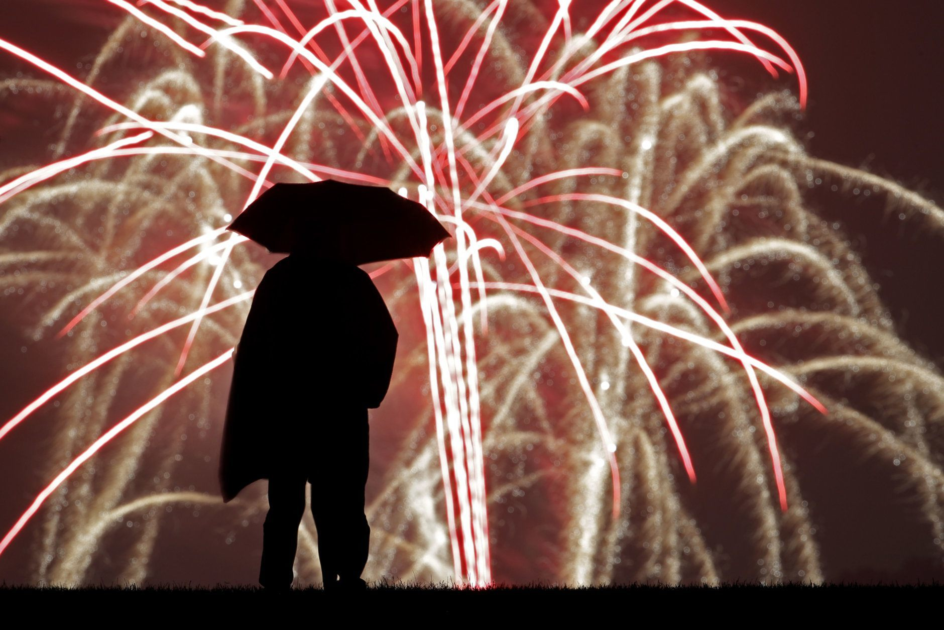 A person watches Independence Day fireworks celebrations from the Liberty Memorial Thursday, July 4, 2019, in Kansas City, Mo. (AP Photo/Charlie Riedel)