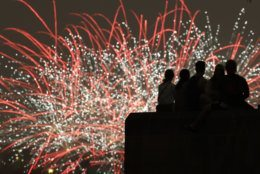 People watch Independence Day fireworks celebrations from the Liberty Memorial Thursday, July 4, 2019, in Kansas City, Mo. (AP Photo/Charlie Riedel)