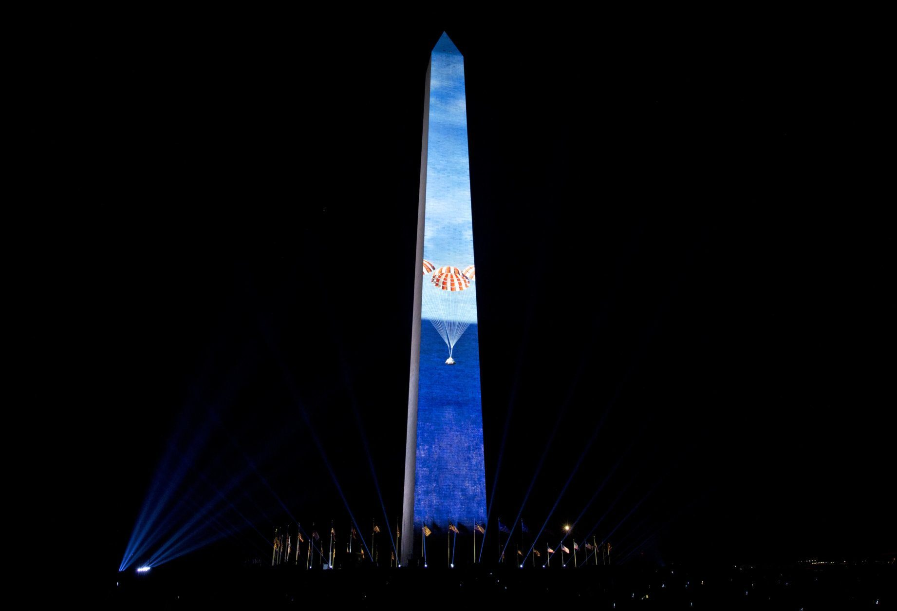 The Apollo 11 mission entering to earth landing with parachutes in the ocean, is projected on the Washington Monument, during the 50th anniversary of the Apollo moon landing festivities at the National Mall in Washington, Friday, July 19, 2019. (AP Photo/Jose Luis Magana)